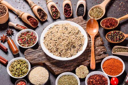 Eine Reihe von Gewürzen und Kräutern. Indische Küche. Pfeffer, Salz, Paprika, Basilikum und andere auf dunklem Hintergrund. Ansicht von oben. Freier Kopienraum