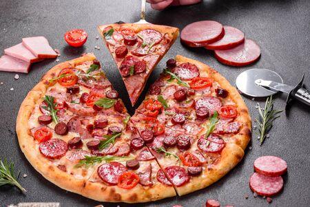 Pizza ai peperoni con mozzarella, salame, prosciutto. Pizza italiana su sfondo scuro