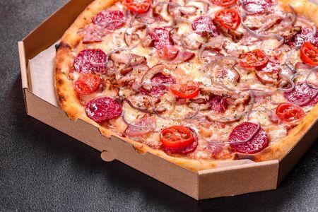 Pizza de pepperoni con queso mozzarella, salami, jamón. Pizza italiana sobre un fondo oscuro