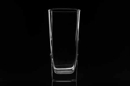 Empty transparent beer glass isolated on black background. Glass tumbler on black background