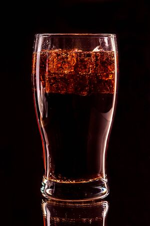 Cola glass with ice cubes and droplets, isolated on black background Standard-Bild - 140647049