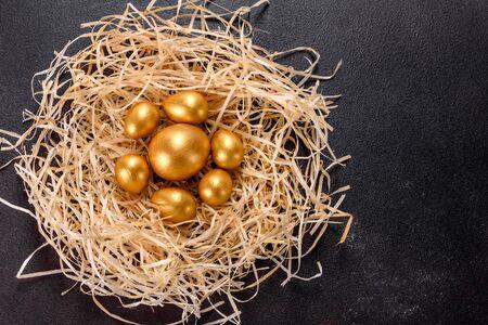 Easter golden eggs in the nest, preparation for the holiday. Golden eggs in nest on dark vintage background