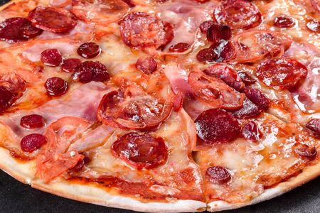 Pepperoni pizza with mozzarella cheese, salami, tomatoes, pepper and spices. Italian cuisine