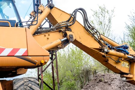 Yellow excavator on a construction site against blue sky. The modern excavator performs excavation work on the construction site