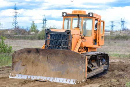 Industrial building construction site bulldozer leveling and moving soil during highway building. Yellow bulldozer at a loamy construction site