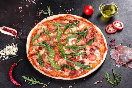 Fresh pizza baked in oven with arugula, salami, cherry tomatoes and mozzarella. Italian cuisine Stock Photo