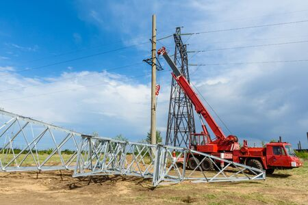 Installation of column for high-voltage electricity line against the background of blue sky on a sunny summer day