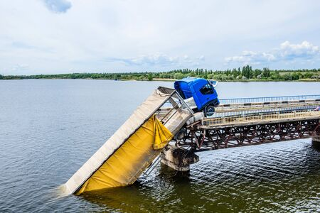 Destruction of bridge structures across the river with the collapse of sections into the water. Truck accident on destroyed bridge