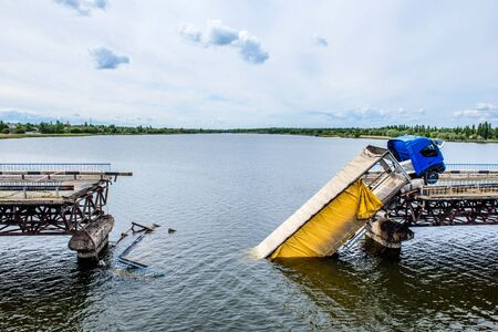 Destruction of bridge structures across the river with the collapse of sections into the water. Truck accident on destroyed bridge Banque d'images