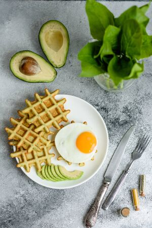 Fresh delicious and nutritious breakfast with waffles with spinach, fried egg and avocado pieces