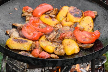 Fresh vegetables are cooked in a grill pan on open fire in the open air