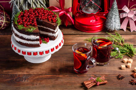 Beautiful delicious cake with bright red berries on the Christmas table with fragrant mulled wine with spices