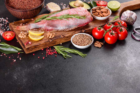 Raw fillet of red sea perch prepared for baking with spices and herbs on a dark background Banque d'images