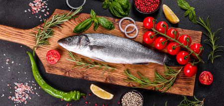 Fresh fish seabass and ingredients for cooking. Raw fish seabass with spices and herbs on a dark table