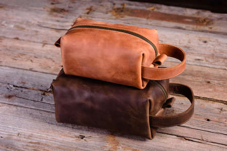 Old vintage leather bag with leather strap. Beautiful small women's leather bag on a wooden background