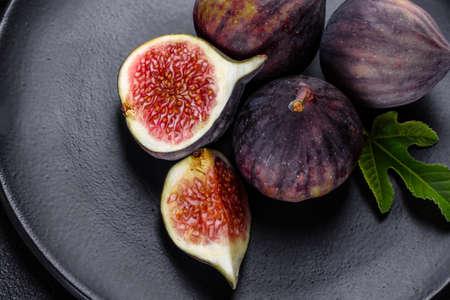 Fresh ripe figs on dark table. Healthy mediterranean fig fruit. Fresh figs on black background