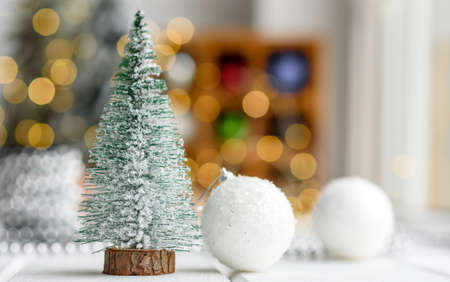 Beautiful multi-colored Christmas decorations on a light wooden table with garlands and Christmas trees in the background. Preparing for the holiday