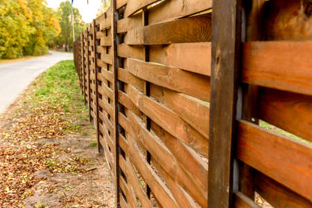 An old fence of wooden planks around a plot of land located near the road