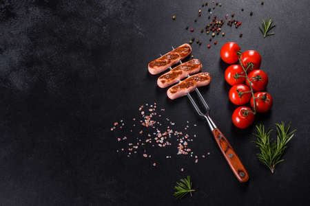 Tasty, fresh sausages grilled with vegetables spices and herbs. Photo of the finished dish on a dark concrete table
