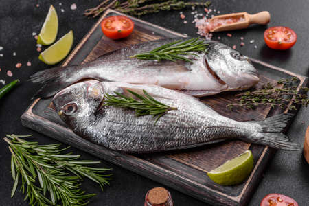 Raw dorado fish with spices cooking on cutting board. Reklamní fotografie