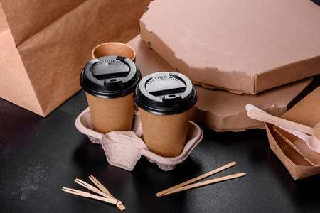 Disposable dishes made of environmentally friendly brown cardboard on a dark background. Food delivery in disposable dishes Imagens