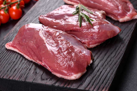 Raw duck with herbs and spices on a dark concrete background. Raw meat prepared for baking