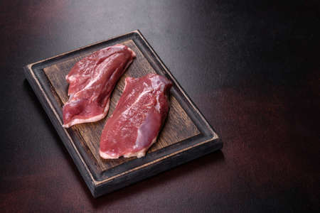 Raw duck breast with herbs and spices on a dark concrete background. Raw meat prepared for baking Stockfoto - 168132331