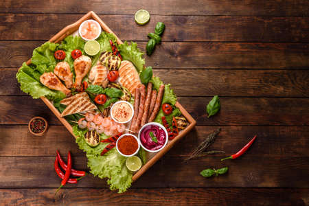 Composition of sausages, chicken, pork and shrimp prepared on grill, as well as vegetables prepared on grill with spices and herbs. Cooking on fire