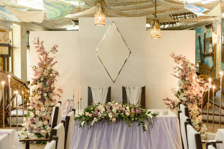 Beautiful floral compositions in the restaurant for the wedding ceremony. Solemn ceremony of painting the groom and bride Stock Photo