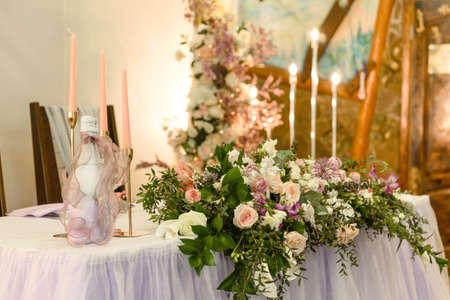Beautiful floral compositions in the restaurant for the wedding ceremony. Solemn ceremony of painting the groom and bride