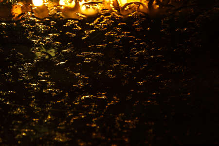 Night lights through the glass with raindrops