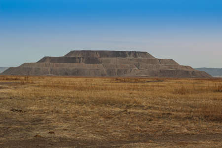 extracted: Industrial pyramid of earth extracted in the quarry. Mountain waste rock in the shape a pyramid.