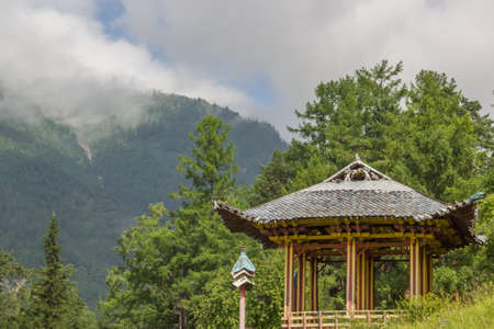 Gazebo in the Buddhist style on the background of green forest and mountains in the fog.