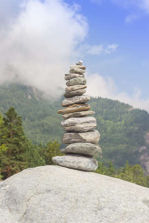 Pyramid from stones on the river bank against a mountain landscape.