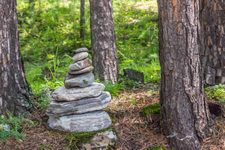 A pyramid of stones in the forest among the trees. Standard-Bild