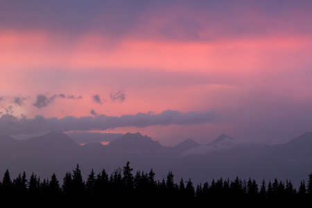 Sunset against mountains in clouds Standard-Bild