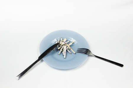 Blue plate with cigarette butts and cutlery.