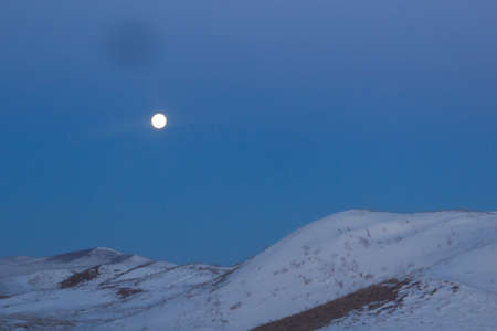The moon against the background of snow mountains and the blue sky.