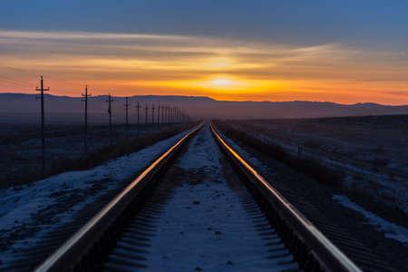 Railway receding into the distance at sunrise