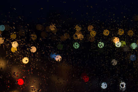Rain drops on the glass colored lights at night. Standard-Bild