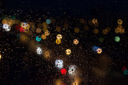 shiny car: Rain drops on the glass colored lights at night. Stock Photo
