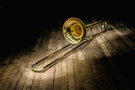 golden brass instrument trombone lies on a dark brown wooden stage in the rays of light
