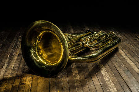 golden brass wind instrument euphonium lies on a brown wooden stage in the light of a spotlight