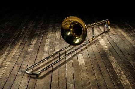 golden brass instrument trombone lies on a brown wooden stage