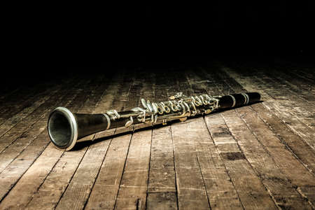 a black woodwind clarinet lies on a dark brown wooden stage in the rays of light
