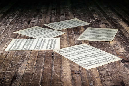 music sheets with notes of a musical work lie on the old floor in the dark