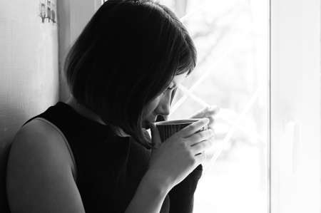 black and white portrait of a young brunette girl in black with a big cup of tea by the window
