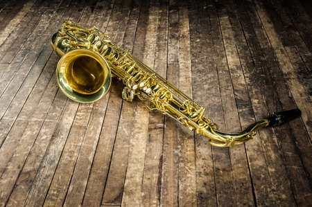 yellow saxophone musical instrument lies on a wooden floor