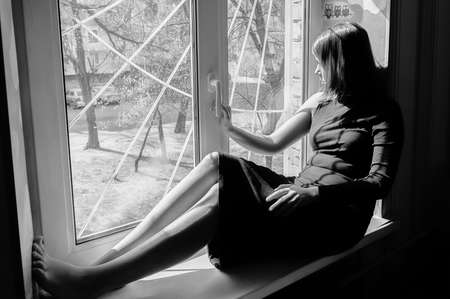 black and white portrait of a beautiful black-haired girl sitting on a windowsill in a long tight-fitting dark dress