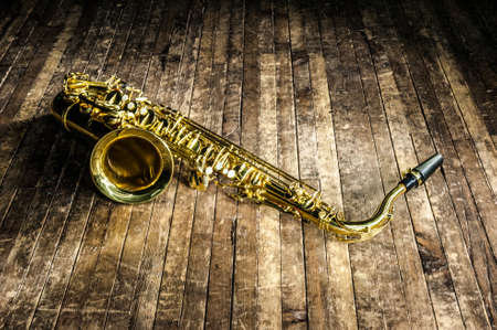 yellow jazz musical instrument saxophone lies on a wooden brown stage